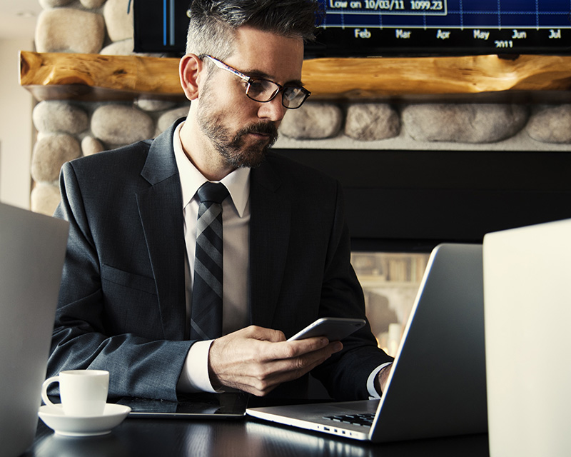 Businessman using laptop and cell phone in a coffee shop